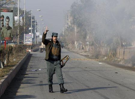 An Afghan policeman reacts as smoke billows during an attack near the Pakistani consulate in Jalalabad, Afghanistan January 13, 2016.  REUTERS/ Parwiz