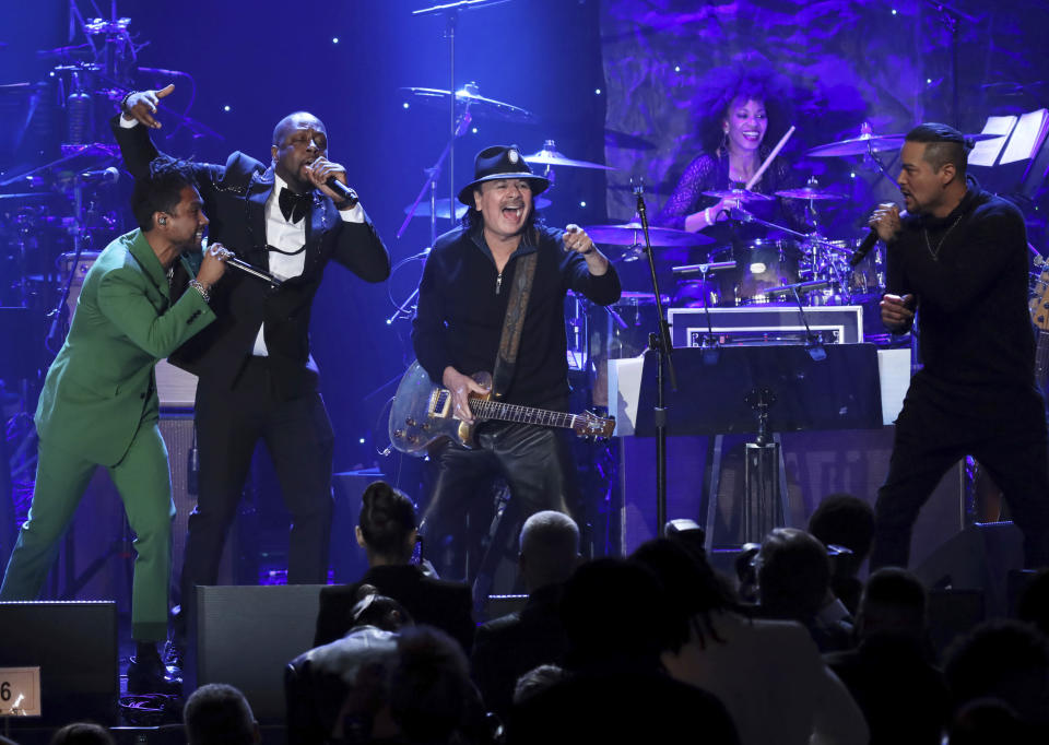 Miguel, from left, Wyclef Jean, Santana, and Andy Vargas perform on stage at the Pre-Grammy Gala And Salute To Industry Icons at the Beverly Hilton Hotel on Saturday, Jan. 25, 2020, in Beverly Hills, Calif. (Photo by Willy Sanjuan/Invision/AP)