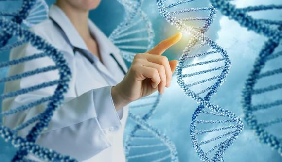 Female researcher pointing to a strand of DNA.