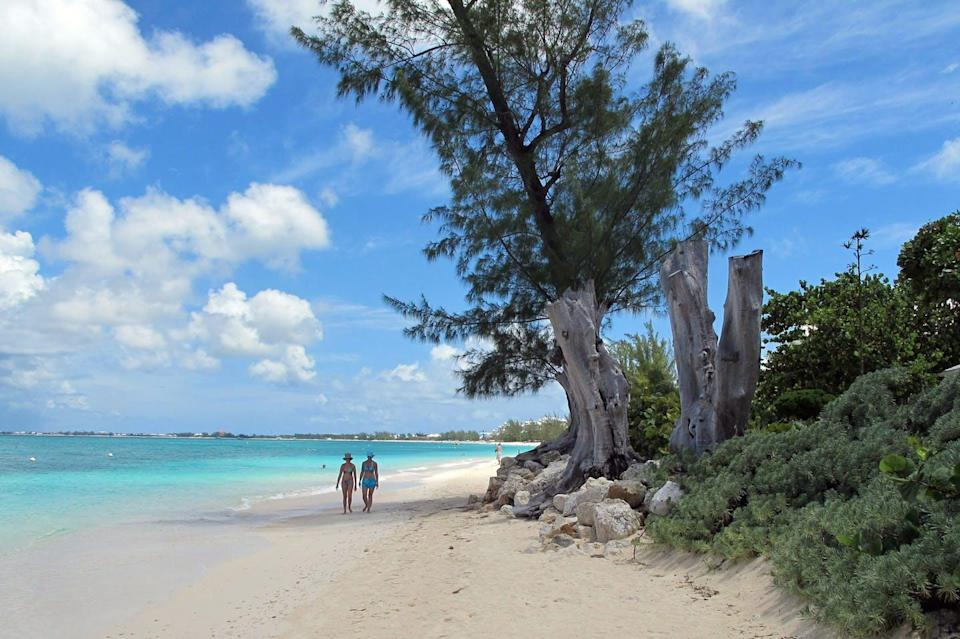 Two tourists walk along a white-sand beach lined with trees and shrubs.