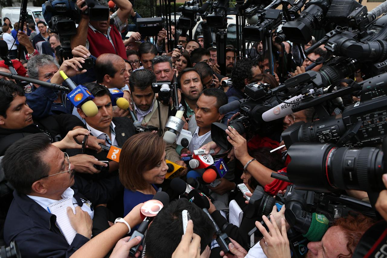 Josefina Vazquez Mota, presidential candidate of the ruling National Action Party (PAN), is surrounded by reporters outside a polling station, after casting her vote during the general elections in Huixquilucan, Mexico, Sunday, July 1, 2012. Mexico's more than 79 million voters head to the polls Sunday to elect a president, who serves one six-year term, as well as 500 congressional deputies and 128 senators. (AP Photo/Andres Leighton)