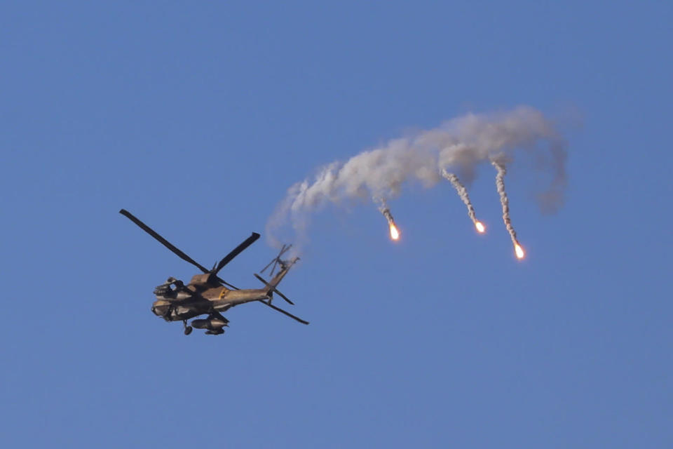 An Israeli attack helicopter launches flares as he flies over the Israeli Gaza border, southern Israel, Thursday, May 13, 2021. (AP Photo/Ariel Schalit)