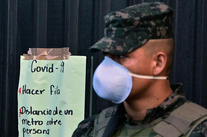 A soldier wearing a face mask stands next to a sign about preventive measures to stop the spread of COVID-19 in Honduras. The government declared a national curfew on March 16, 2020. (Photo: ORLANDO SIERRA/Getty Images)