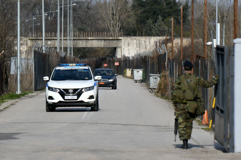 A Greek soldier opens the gate to a police vehicle, at the closed Kastanies border crossing with Turkey's Pazarkule, in the region of Evros