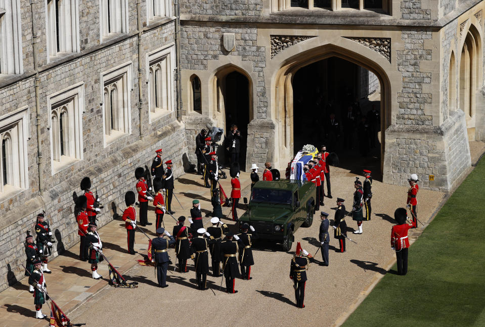 Members of the 1st Battalion Grenadier Guards place the coffin of Britain's Prince Philip onto a modified Jaguar Land Rover in the Quadrangle at Windsor Castle in Windsor, England, Saturday, April 17, 2021 ahead of the funeral of Britain's Prince Philip. Prince Philip died April 9 at the age of 99 after 73 years of marriage to Britain's Queen Elizabeth II. (Adrian Dennis/Pool via AP)