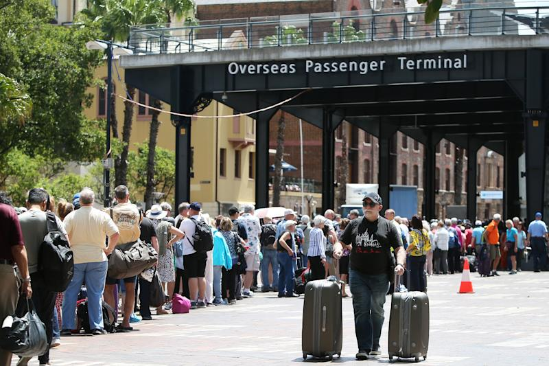 Passengers queue at the Overseas Passenger Terminal as the Norwegian Jewel cruise ship is docked while health authorities test a man for coronavirus.
