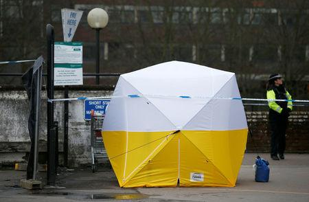A police officer stands behind a cordon placed around a payment machine covered by a tent in a supermarket car park near to where former Russian intelligence agent Sergei Skripal and his daughter Yulia were found poisoned in Salisbury