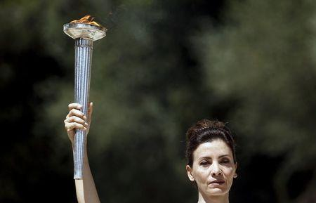 Greek actress Katerina Lehou, playing the role of High Priestess, holds an Olympic torch during the dress rehearsal for the Olympic flame lighting ceremony for the Rio 2016 Olympic Games at the site of ancient Olympia in Greece, April 20, 2016. REUTERS/Yannis Behrakis