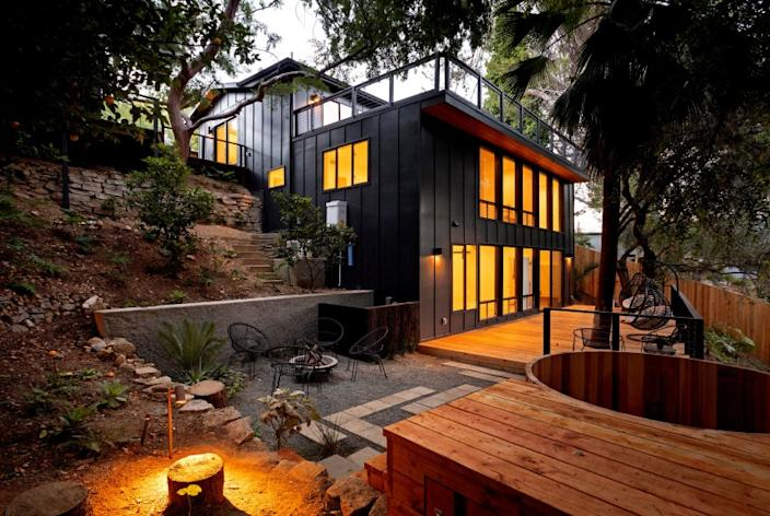 """Listed for $2.149 million, the renovated home in Mount Washington presents as a modern treehouse with expansive decking that incorporates a number of mature trees into its design. Renovated by L.A.-based firm KeltnerCo, the three-bedroom, four-bathroom house has a casual feel with open-concept living areas, light hardwood floors and a mostly white-walled interior. The new-look kitchen is anchored by an island/breakfast bar topped with dark-hued Calacatta marble. The living room, which has a three-sided fireplace, sits nearby. Decking on multiple levels creates more than 700 square feet of additional space. A detached studio and a cedar spa lie elsewhere on the grounds. <span class=""""copyright"""">(Alex Zarour)</span>"""