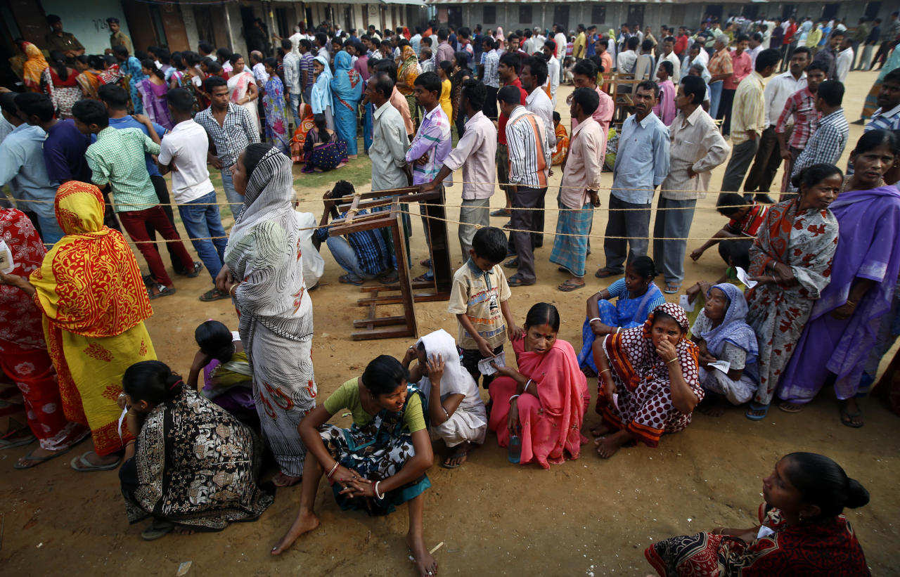 People wait in queue to cast their votes during the first phase of elections in Agartala, in the northeastern state of Tripura, India, Monday, April 7, 2014. India started the world's largest election Monday, with voters in the remote northeast making their way past lush rice paddies and over rickety bamboo bridges to reach the polls. The country's 814 million electorate will vote in stages over the next five weeks. (AP Photo/Saurabh Das)