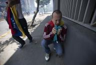 A demonstrators kneels on the ground overwhelmed by tear gas fired by the Bolivarian the National Police in Caracas, Venezuela, Saturday, April 8, 2017. Opponents of President Nicolas Maduro protest on the streets of Caracas on Saturday as part of a week-long protest movement that shows little sign of losing steam. (AP Photo/Ariana Cubillos)