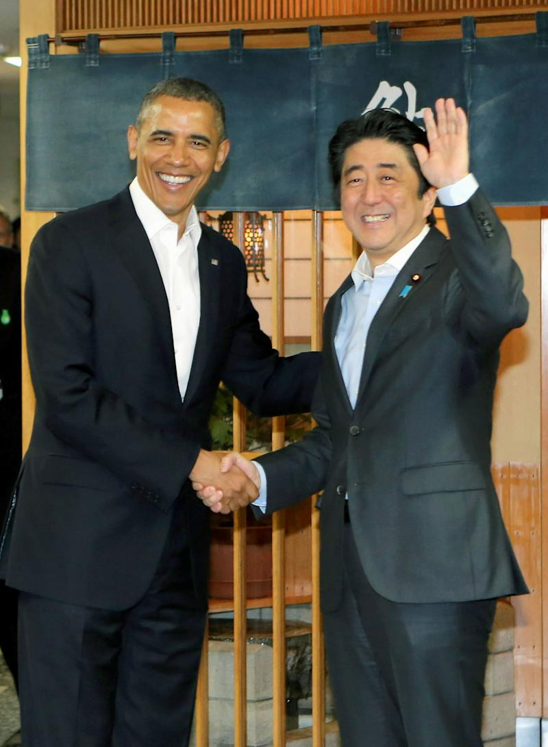Obama and Abe shake hands in front of Sukiyabashi Jiro sushi restaurant.