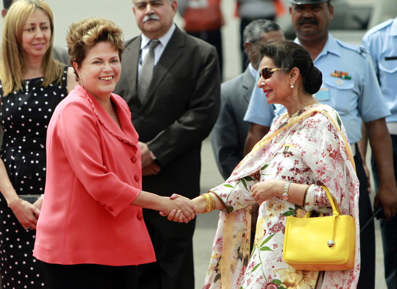 Brazil's President Dilma Rousseff, left, is greeted by India's Junior Minister for External Affairs Preneet Kaur at the Palam Technical Airport in New Delhi, India, Tuesday, March 27, 2012. Rousseff is in India attending the BRICS (Brazil, Russia, India, China, South Africa) Summit which is to be held March 29 in New Delhi.  (AP Photo/ Mustafa Quraishi)