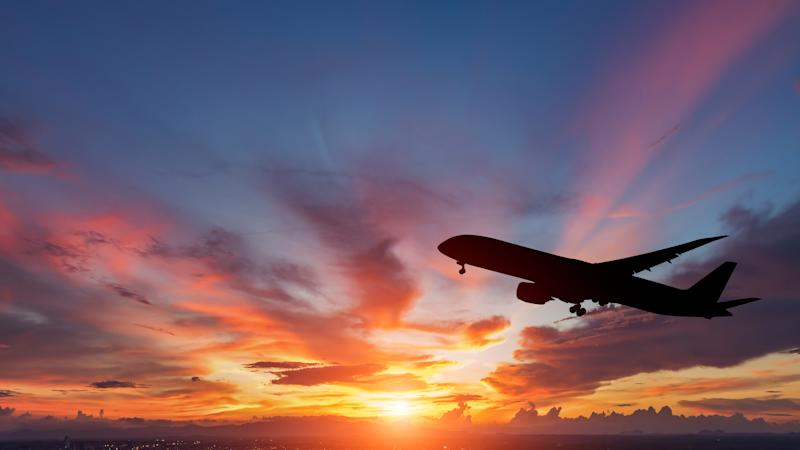 Silhouette of an airplane with sun setting and clouds in the background