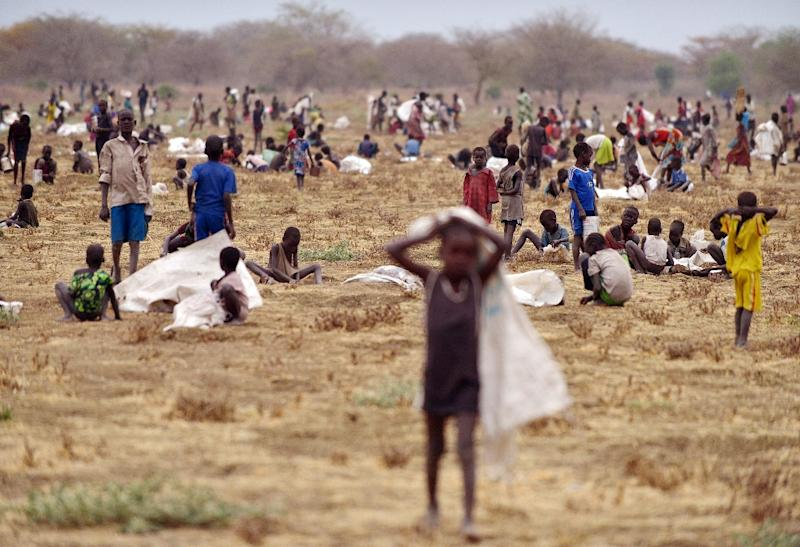 Children flock with containers to a field demarcated for food-drops at a village in Nyal, an administrative hub of Panyijar county in Unity state, South Sudan, on February 24, 2015 (AFP Photo/Tony Karumba)