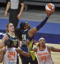 Dallas Wings guard Arike Ogunbowale scores over Connecticut Sun defenders DeWanna Bonner (24) and Emma Cannon (32) during a WNBA basketball game Tuesday, June 22, 2021, at Mohegan Sun Arena in Uncasville, Conn. (Sean D. Elliot/The Day via AP)