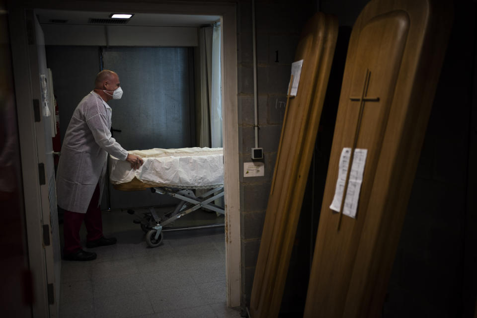A mortuary worker prepares a coffin carrying the body of a person who died of COVID-19 during a funeral at Memora mortuary in Girona, Spain, Thursday, Feb. 4, 2021. So far in the vaccine race UK vaccination stats have a rate of 15 percent compared to some 3 percent in the EU bloc. The EU has already lost some 480,000 citizens to the pandemic in a bloc of 450 million with more fatalities mounting by the day. (AP Photo/Emilio Morenatti)