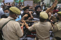 Activists of Peoples Democratic Party scuffle with police during protest marking the second anniversary of Indian government scrapping Kashmir's semi- autonomy in Jammu, India, Thursday, Aug. 5, 2021. On Aug. 5, 2019, Indian government passed legislation in Parliament that stripped Jammu and Kashmir's statehood, scrapped its separate constitution and removed inherited protections on land and jobs. (AP Photo/Channi Anand)