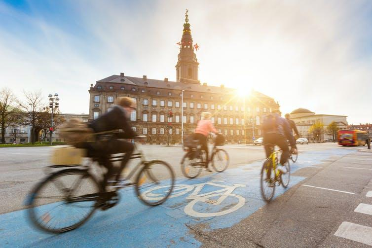 Three people commute by bike on a morning in Copenhagen.