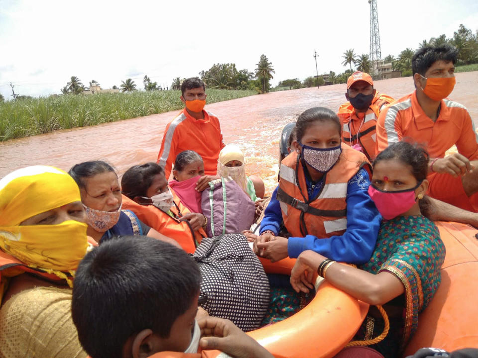 This photograph provided by India's National Disaster Response Force (NDRF) shows NDRF personnel rescuing flood affected women and children at Kolhapur in the western Indian state of Maharashtra, Sunday, July 25, 2021. Officials say landslides and flooding triggered by heavy monsoon rain have killed more than 100 people in western India. (National Disaster Response Force via AP)