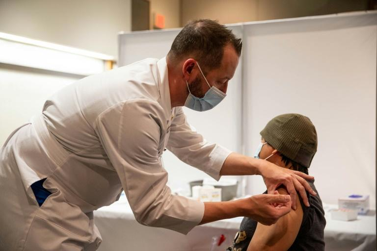 Jeff Doucette, a chief nursing officer, administers a Covid-19 vaccine to a nurse at Thomas Jefferson University Hospital in Philadelphia