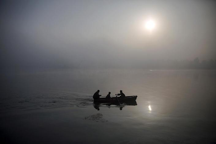 <p>North Korean military personnel paddle a small boat amid morning fog over Taedong River in Pyongyang, Oct. 8, 2015. (Damir Sagolj/Reuters) </p>