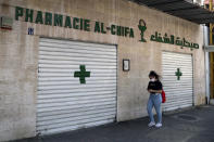 A woman passes by a closed pharmacy in Beirut, Lebanon, Friday, June 11, 2021. Pharmacies across Lebanon began a two-day strike Friday, protesting severe shortages in medicinal supplies that is increasingly putting them in confrontation with customers and patients searching for medicines. The shortages are affecting everything from medicines for chronic illnesses to pain relievers to infant milk. (AP Photo/Bilal Hussein)