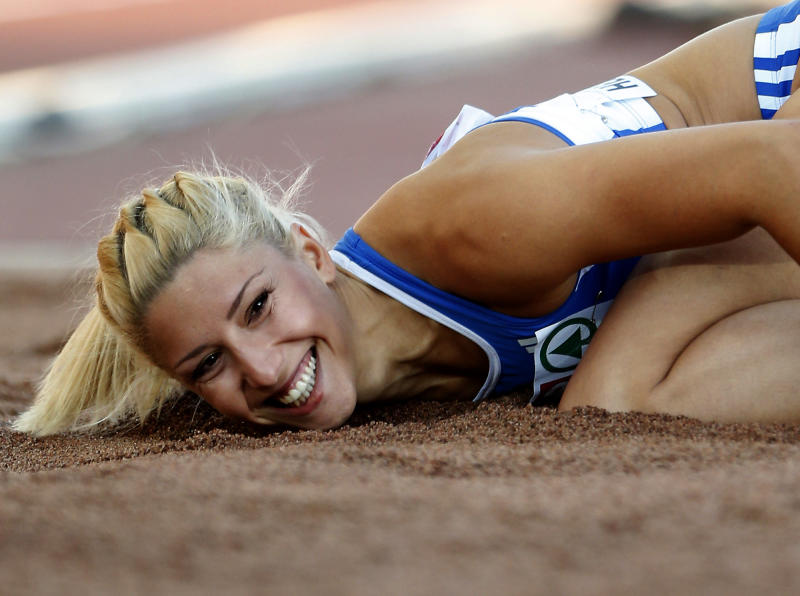 """FILE- Greece's Voula Papachristou lands in the sand after her jump at the Women's Triple Jump final at the European Athletics Championships in Helsinki, Finland, in this file photo dated Friday, June 29, 2012. The Hellenic Olympic Committee has removed triple jumper Voula Papachristou from the team taking part in the upcoming London Olympic Games over comments she made on twitter making fun of African immigrants and expressing support for a far-right party. """"The track and field athlete Paraskevi (Voula) Papachristou is placed outside the Olympic Team for statements contrary to the values and ideas of the Olympic movement,"""" a statement by the Hellenic Olympic Committee says. Papachristou is in Athens, and was to travel to London """"shortly before the track events start,"""" the announcement says.(AP Photo/Matt Dunham, file)"""