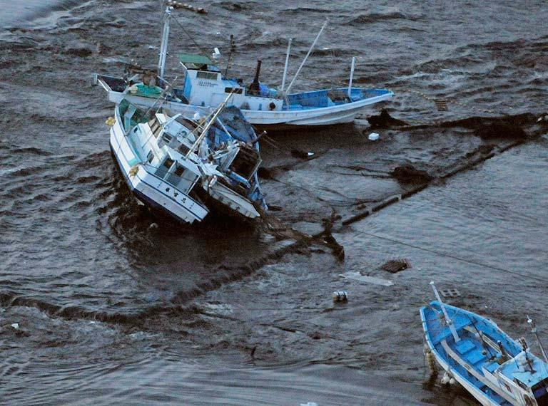 Fishing boats get stranded on shore at Oarai town, Ibaraki prefecture (state), Japan, after a ferocious tsunami spawned by one of the largest earthquakes ever recorded slammed Japan's eastern coasts Friday, March 11, 2011. (AP Photo/Kyodo News)