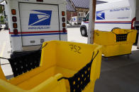 """Mail delivery vehicles are parked outside a post office in Boys Town, Neb., Tuesday, Aug. 18, 2020. The Postmaster general announced Tuesday he is halting some operational changes to mail delivery that critics warned were causing widespread delays and could disrupt voting in the November election. Postmaster General Louis DeJoy said he would """"suspend"""" his initiatives until after the election """"to avoid even the appearance of impact on election mail."""" (AP Photo/Nati Harnik)"""