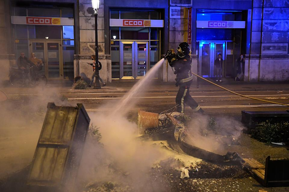 A firefighter douses burning trash after clashes erupted between members of the Catalan regional police force Mossos d'Esquadra and protesters during a demonstration against new coronavirus restrictions in Barcelona on October 30, 2020. - One by one, Spain's regions have announced regional border closures in the hope of avoiding a new lockdown like in France. The central government unveiled a state of emergency to give regional authorities the tools to impose curfews and close their borders to anyone moving without just cause. (Photo by Josep LAGO / AFP) (Photo by JOSEP LAGO/AFP via Getty Images)
