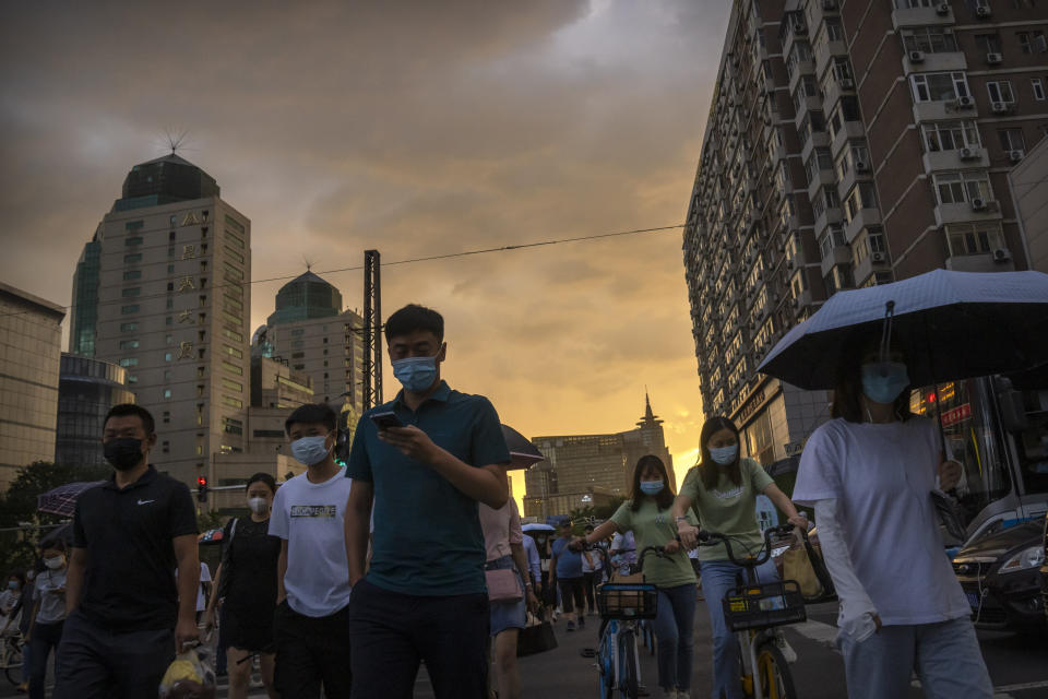 People wearing face masks to protect against COVID-19 walk across an intersection during the evening rush hour in Beijing, Thursday, Aug. 26, 2021. (AP Photo/Mark Schiefelbein)
