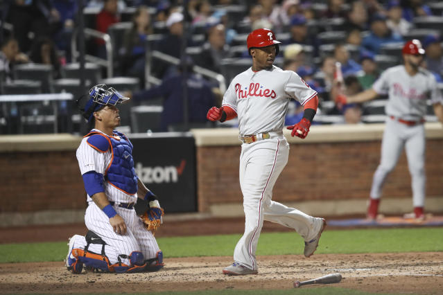 Philadelphia Phillies' Jean Segura, center, scores on an RBI-double by J.T. Realmuto during the fifth inning of a baseball game against the New York Mets, Friday, Sept. 6, 2019, in New York. (AP Photo/Mary Altaffer)