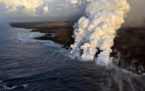 Lava pours into the sea on the south margin of the fissure 8 flow of the K?lauea volcano - Credit: AFP