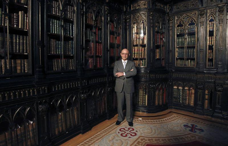 Spain's Treasury Minister Cristobal Montoro poses for pictures at the Senate Library before an interview with Reuters in Madrid