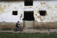Milan Bastyur, a 4 year old Hungarian Roma child, rides a bike outside his family's home in Bodvaszilas, Hungary, Monday, April 12,2021. Many students from Hungary's Roma minority do not have access to computers or the internet and are struggling to keep up with online education during the pandemic. Surveys show that less than half of Roma families in Hungary have cable and mobile internet and 13% have no internet at all. (AP Photo/Laszlo Balogh)