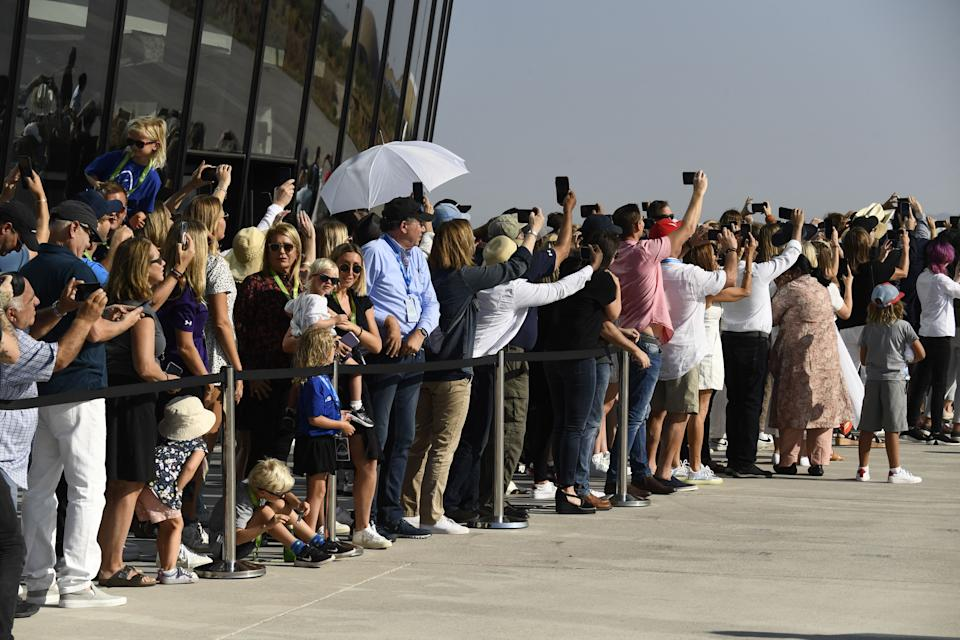 Spectators take photos and cheer as the Virgin Galactic SpaceShipTwo space plane Unity takes off at Spaceport America, near Truth and Consequences, New Mexico on July 11, 2021  before travel to the cosmos. - Billionaire Richard Branson takes off on July 11, 2021 from a base in New Mexico aboard a Virgin Galactic vessel bound for the edge of space, a voyage he hopes will lift the nascent space tourism industry off the ground.A massive carrier plane made a horizontal take-off from Space Port, New Mexico at around 8:40 am Mountain Time (1440 GMT) and will ascend for around an hour to an altitutude of 50,000 feet (15 kilometers). The mothership will then drop a rocket-powered spaceplane called VSS Unity, which will ignite its engine and ascend at Mach 3 beyond the 50 miles (80 kilometers) carrying two pilots and four passengers, including Branson. (Photo by Patrick T. FALLON / AFP) (Photo by PATRICK T. FALLON/AFP via Getty Images)