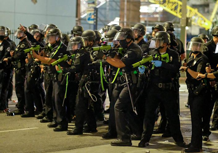 Police officers prepare to fire rubber bullets during a protest over the death of George Floyd, Friday, May 29, 2020 in Los Angeles.