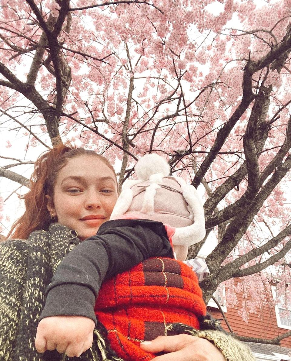 """<p>In one selfie, Hadid carried a bundled up Khai while <a href=""""https://www.instagram.com/p/CN3i4cXnMqN/"""" rel=""""nofollow noopener"""" target=""""_blank"""" data-ylk=""""slk:showing off a blossoming tree"""" class=""""link rapid-noclick-resp"""">showing off a blossoming tree</a>. </p>"""