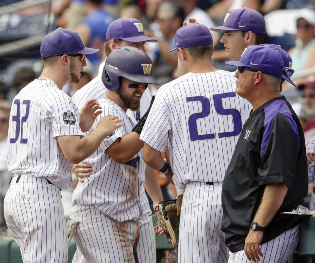 Washington's Nick Kahle, center, is congratulated at the dugout by Leo Nierengerg (32) and Jack Johnson (25) after he scored against Oregon State on a single by Joe Wainhouse in the third inning of an NCAA College World Series baseball elimination game in Omaha, Neb., Monday, June 18, 2018. (AP Photo/Nati Harnik)