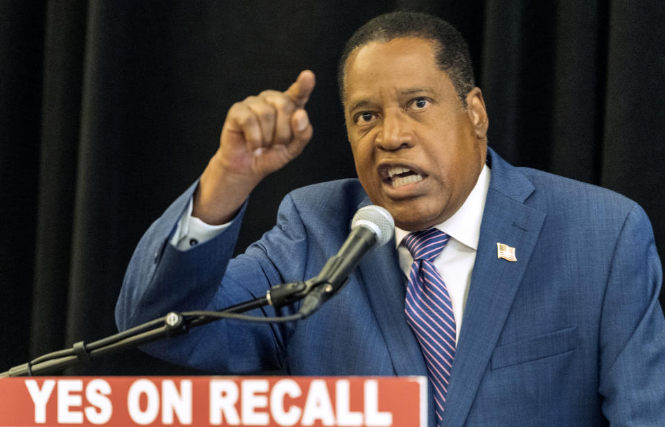 Republican conservative radio show host Larry Elder speaks into a microphone at a podium with a sign reading: Yes on recall