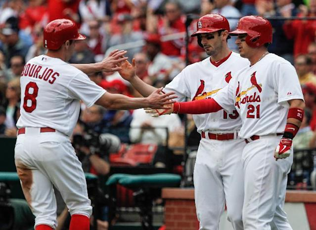 St. Louis Cardinals Matt Carpenter, center, celebrates with Peter Bourjos, left, and Allen Craig, right, after they scored on Michael Wacha's two-run single in the second inning of a baseball game against the Chicago Cubs Thursday, May 15, 2014, in St. Louis. (AP Photo/Sarah Conard)