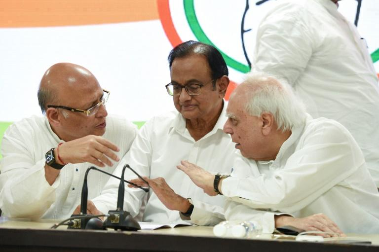 India's former finance minister and Congress party leader P. Chidambaram (C) talks with other leaders Kapil Sibal (R) and Abhishek Manu Singhvi at the party headquarters in New Delhi on August 21, 2019 -- Chidambaram was later reportedly arrested