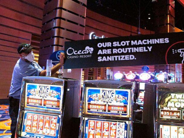 PHOTO:A worker at the Ocean Casino Resort in Atlantic City N.J., June 3, 2020, installs a sign indicating that slot machines will routinely be sanitized once the casino reopens to prevent the spread of the coronavirus. (Wayne Parry/AP)