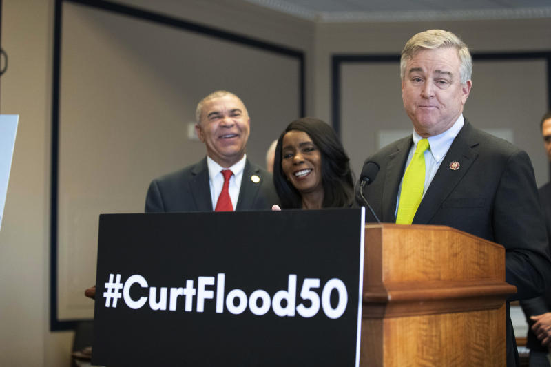 Rep. William Lacy Clay, D-Mo., left, and Judy Pace Flood, listen as Rep. David Trone, D-Md., right, speaks during a news conference as they call for the late Curt Flood to be inducted into the Baseball Hall of Fame, on Capitol Hill, Thursday, Feb. 27, 2020 in Washington. (AP Photo/Alex Brandon)