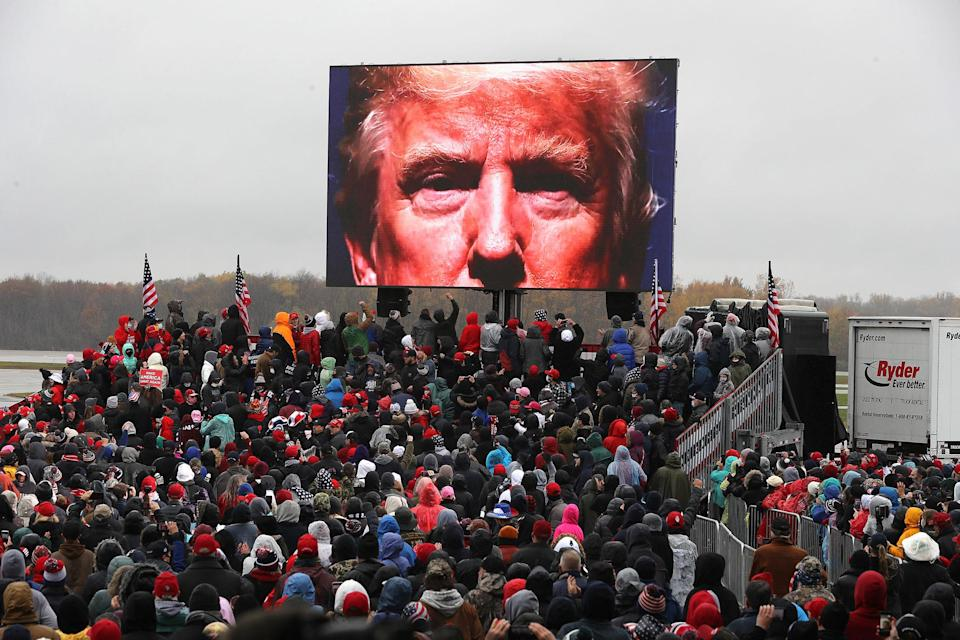 Supporters watch a video of President Donald Trump while waiting for his arrival at a campaign rally at Capital Region International Airport in Lansing, Mich. on Oct. 27, 2020.