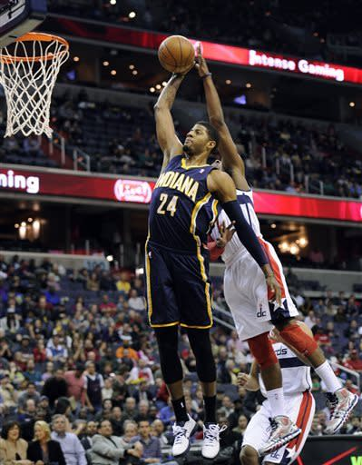 Indiana Pacers forward Paul George (24) goes to the basket against Washington Wizards guard John Wall, right, during the first half of an NBA basketball game, Saturday, April 6, 2013, in Washington. Wall was called for a foul on the play. (AP Photo/Nick Wass)