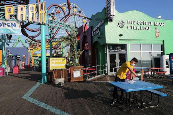PHOTO: A worker cleans a table on Santa Monica Pier amid the COVID-19 pandemic on July 2, 2020 in Santa Monica, Calif. (Mario Tama/Getty Images)