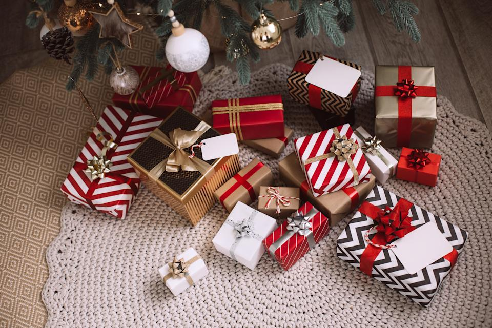 Stack of Christmas presents with tags for big family under Christmas tree with decorations and lights. Stylish striped wrapping in black, white and red colors. Home interior in New Year's eve
