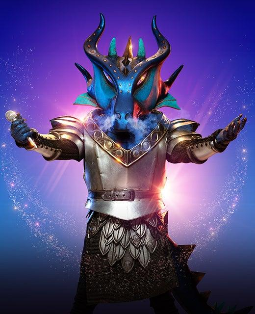 Promo picture from The Masked Singer showing the Dragon holding a microphone with open arms.